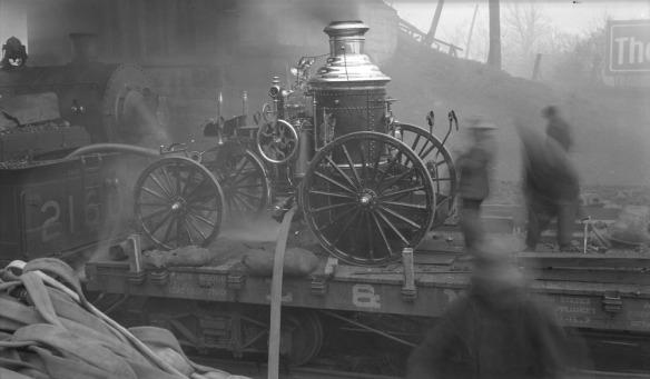 Photographie en noir et blanc d'une pompe à incendie à vapeur sur un wagon plat. Des hommes utilisent la pompe pour combattre un incendie près d'une voie ferrée et de remises.