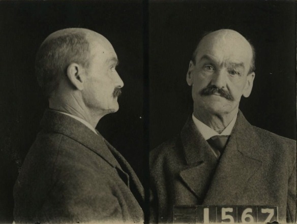 Une photo signalétique en noir et blanc montrant un homme avec un peu de calvitie et une moustache vue de profile et de l'avant. Il tient une affiche avec le numéro 1567.