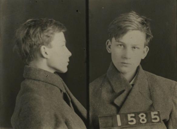 Une photo signalétique en noir et blanc montrant un très jeune homme vu de profile et de l'avant. Il tient une affiche avec le numéro 1585.