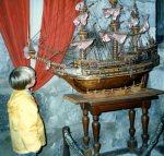 Photo en couleur d'un jeune garçcon regardant un modèle réduit d'un navire.