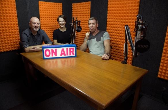 Photo couleur de deux hommes et une femme, assis dans un studio d'enregistrement avec un panneau sur lequel on peut lire : « On Air » [À l'antenne]