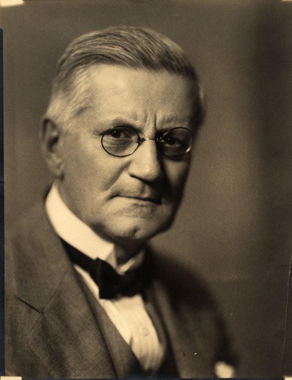 Photographie en noir et blanc d'un homme d'âge avancé portant un nœud papillon et des lunettes.