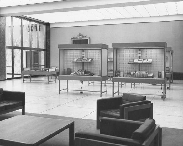 Photographie en noir et blanc d'une grande salle où des livres sont exposés dans des présentoirs vitrés.