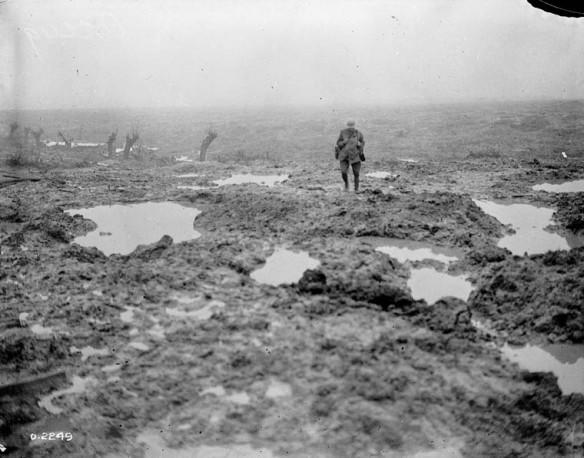 Photographie en noir et blanc d'un soldat marchant dans un champ couvert de boue et de flaques d'eau.