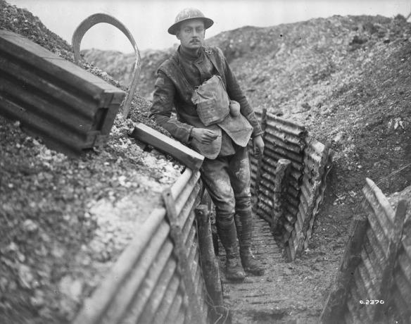 Photo noir et blanc d'un soldat couvert de boue, appuyé au mur d'une tranchée, tenant une cigarette et regardant le photographe.