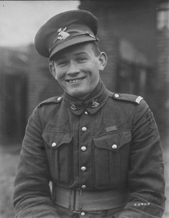 Photo noir et blanc d'un jeune homme souriant, en uniforme, la casquette légèrement de travers.