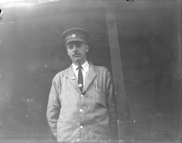 Une photographie en noir et blanc d'un homme portant une casquette, une veste de laine grise, une chemise blanche et une cravate foncée.