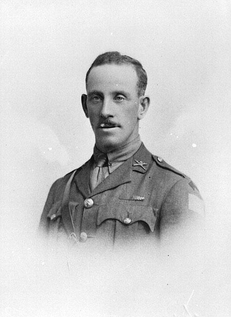 Une photographie en noir et blanc d'un soldat en uniforme portant une petite moustache.