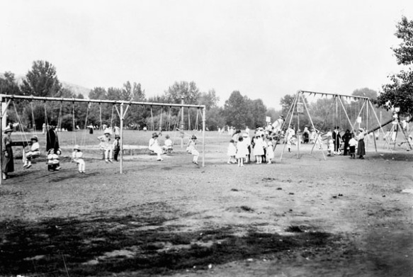 Photographie en noir et blanc d'un parc et d'un terrain de jeu avec deux structures de balançoires et une balançoire à bascule. Des garçons et des fillettes s'y amusent sous la supervision d'adultes.