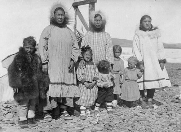 Photographie en noir et blanc d'une famille inuite non identifiée. Huit personnes y figurent : (de gauche à droite) un garçon, une femme, une fillette, une femme, un garçonnet, deux fillettes et une jeune femme.