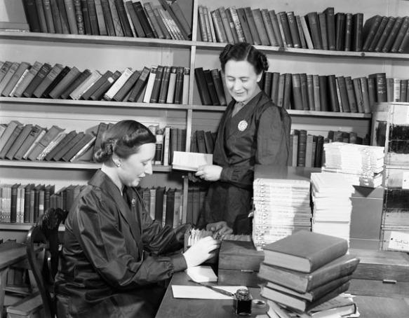 Photographie en noir et blanc de deux femmes dans une bibliothèque. L'une examine un catalogue sur fiches et l'autre tient un livre et regarde l'autre femme travailler.