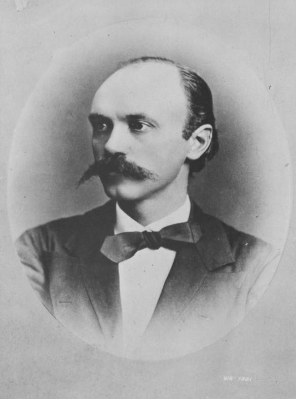 Photo noir et blanc d'un homme à la moustache proéminente portant un veston et un nœud papillon. La photo de forme ovale est placée sur un carton de montage mat de couleur grise.