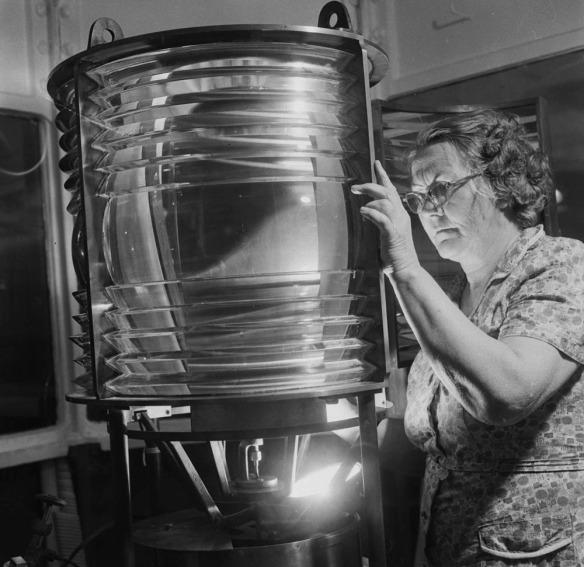 Photographie en noir et blanc d'Eliza Campbell examinant la lampe d'un phare.