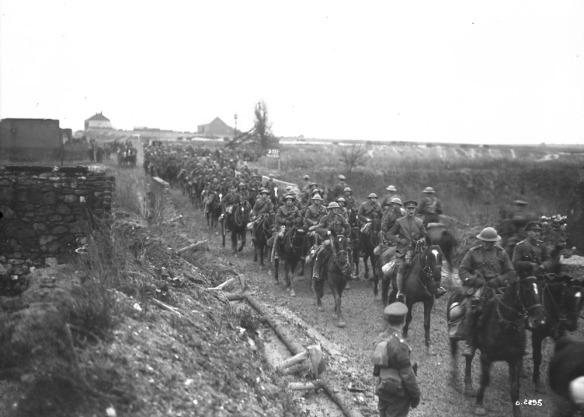Photographie en noir et blanc de soldats à cheval traversant un village.