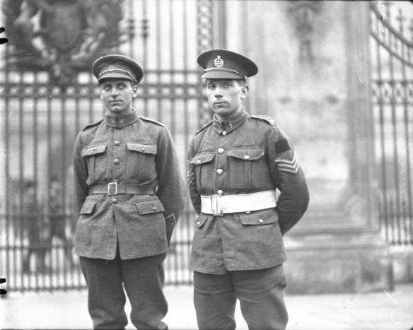 Photo noir et blanc de deux soldats debout devant une grille en fer forgé ouvragé.