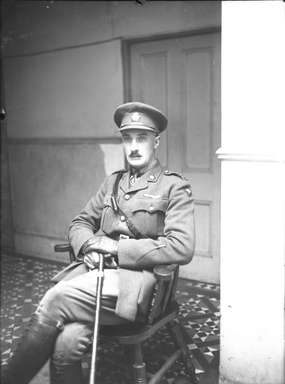 Photographie en noir et blanc d'un officier assis qui porte un couvre-chef et tout l'équipement d'un officier.