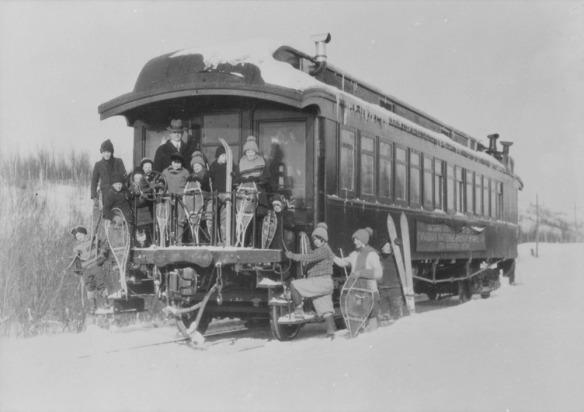 Photographie en noir et blanc de 13 enfants et de leur enseignant posant avec leurs raquettes sur la plateforme d'une voiture de transport scolaire de la Compagnie des chemins de fer nationaux du Canada.