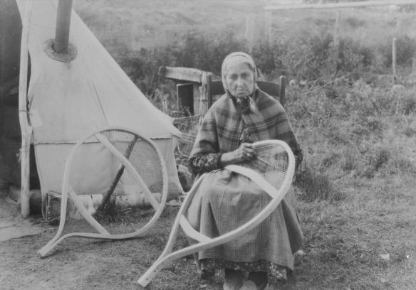 Photographie en noir et blanc d'une femme des Premières Nations non identifiée qui est assise sur une chaise et travaille sur le lacis d'une grande raquette ronde.