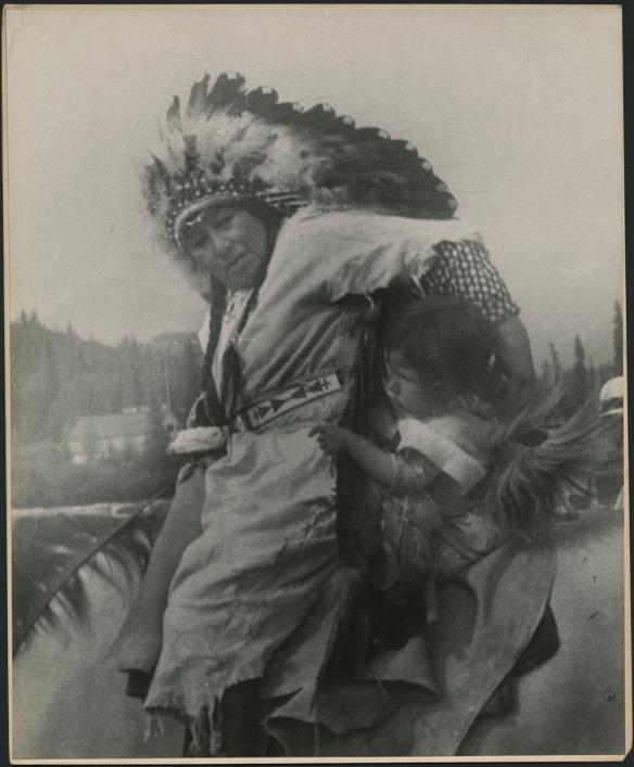 Femme à cheval, tenant une petite fille à ses côtés. La femme porte une tunique unie avec une ceinture à motif; ses cheveux tressés sont ornés d'une coiffe de plumes.