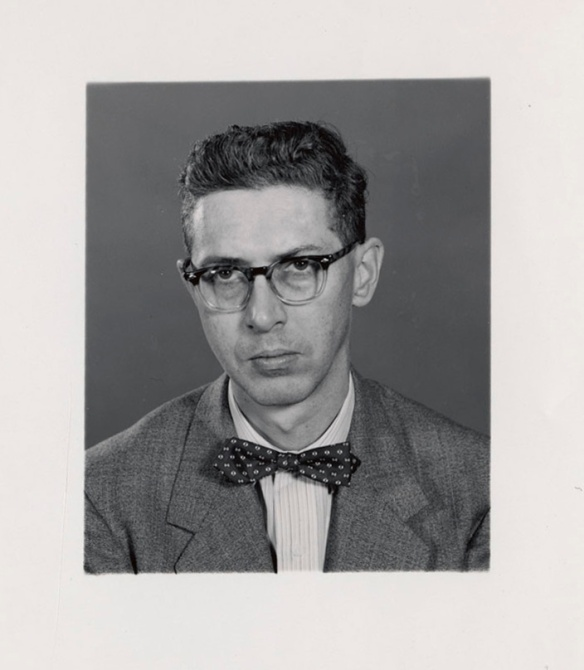 Photo noir et blanc d'un jeune homme portant des lunettes et un nœud papillon et un veston.