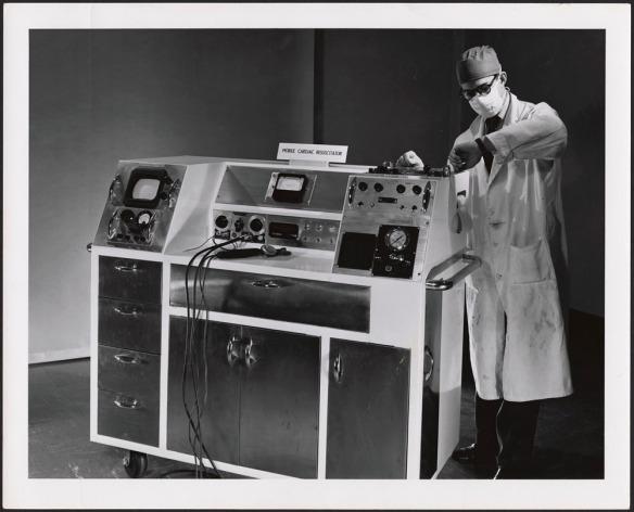 Photo noir et blanc d'un homme portant un sarrau, un masque et un bonnet de chirurgien. Il regarde sa montre, debout à côté d'un gros appareil sur roulettes équipé de nombreux tiroirs, boutons et fils, au sommet duquel un écriteau indique « Mobile Cardiac Resuscitator » (réanimateur cardiaque mobile).