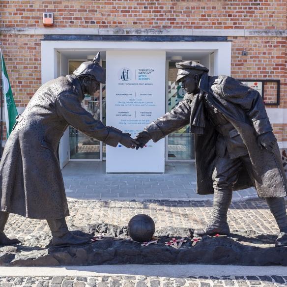 Photo couleur d'une sculpture de deux soldats enemis se tenant la main au-dessus d'un ballon de rugby.