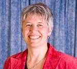 Photo en couleur d'une femme portant un veston rouge devant un rideau bleu et arborant un grand sourire.