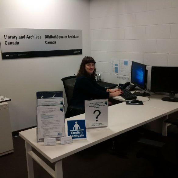Une photographie couleur d'une femme qui est assise à un bureau devant un ordinateur et qui regarde vers l'appareil photo. L'affiche « Library and Archives Canada – Bibliothèque et Archives Canada » est accrochée au mur derrière elle.