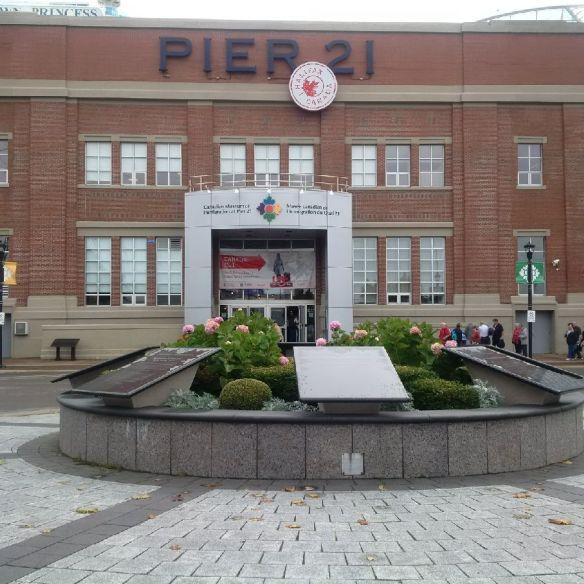 Photographie en couleurs d'un bâtiment en briques rouges arborant la mention « Pier 21 ». Devant l'entrée principale se trouve un jardin surélevé clôturé d'un muret de pierre circulaire soutenant plusieurs grandes plaques.