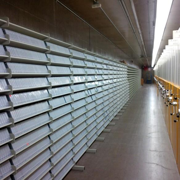 Photographie en couleur d'une longue étagère blanche contenant des milliers de bandes magnétiques sur la gauche et d'éléments de stockage à haute densité à droite.