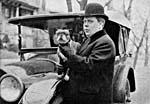 Photographie en noir et blanc d'un homme debout devant une automobile, coiffé d'un chapeau melon et tenant un petit chien dans ses bras.