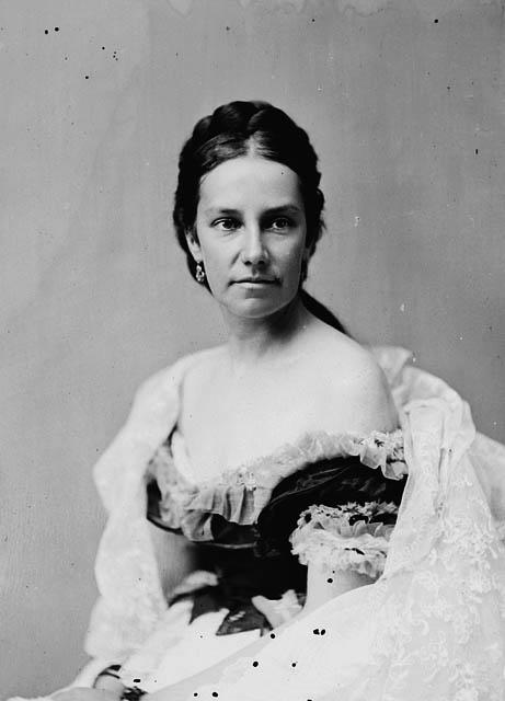 Une photographie en noir et blanc d'une femme qui regarde légèrement vers la gauche. Ses cheveux sont séparés par une raie au milieu et attachés derrière la nuque; elle porte une robe du soir dégageant les épaules.