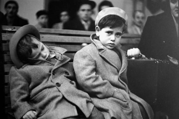 Une photo en noir et blanc de deux jeunes garçons portant des manteaux et des chapeaux de laine, assis sur un banc de bois. L'un s'est écroulé de sommeil; l'autre fixe l'appareil photo et tient une valise. Une foule floue est visible en arrière-plan.