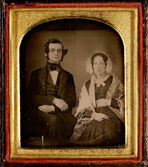 Une photographie couleur d'une image en sépia dans un cadre de bois et d'or présentant un homme et une femme assis. L'homme porte un complet, un gilet et une cravate. La femme porte une charlotte, une robe et un châle à motifs.