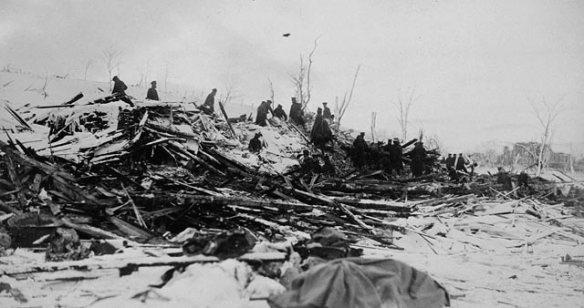 Photographie en noir et blanc montrant une rangée de personnes fouillant les décombres des bâtiments détruits.