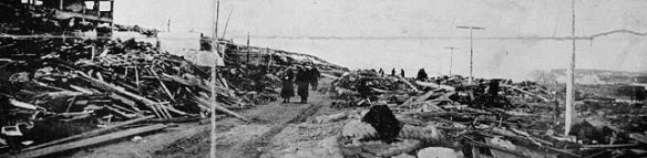 Photographie en noir et blanc de quelques personnes marchant au milieu d'une rue dont les bâtiments sont détruits.