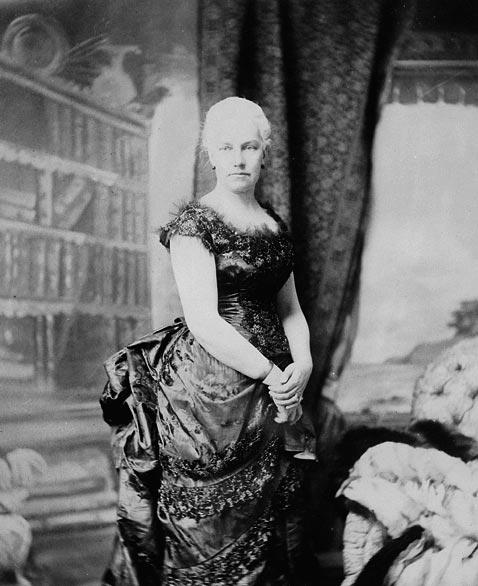 Une photographie en noir et blanc d'une femme portant une robe longue de couleur foncée. Ses cheveux sont blancs et coiffés en chignon.