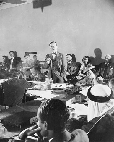 Photographie en noir et blanc d'un homme debout devant une salle pleine de gens auxquels il s'adresse.