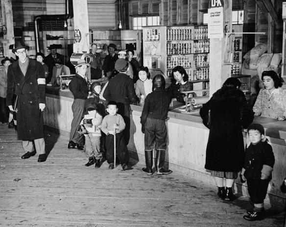Photographie en noir et blanc de Canadiens d'origine japonaise se procurant des articles dans un magasin du camp d'internement de Slocan, en Colombie-Britannique. Un homme blanc portant un brassard les observe.
