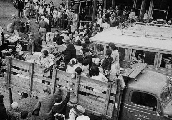 Photographie en noir et blanc de nombreuses familles de Canadiens d'origine japonaise à une aire de rassemblement. Elles prennent place à l'arrière de camions pour leur déplacement vers un camp d'internement de la région intérieure de la Colombie-Britannique.