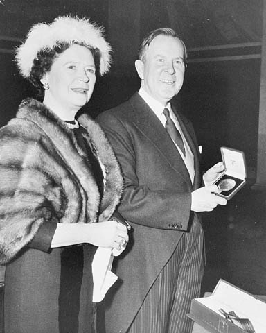 Photographie en noir et blanc d'un couple en tenue soignée. L'homme tient une boîte contenant une médaille.