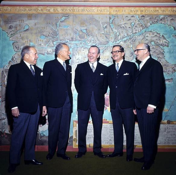 Photographie en couleurs d'un groupe d'hommes debout devant l'agrandissement d'une carte de la Nouvelle-France.