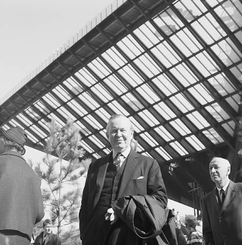 Photographie en noir et blanc d'un homme debout près d'un édifice doté d'une architecture intéressante.