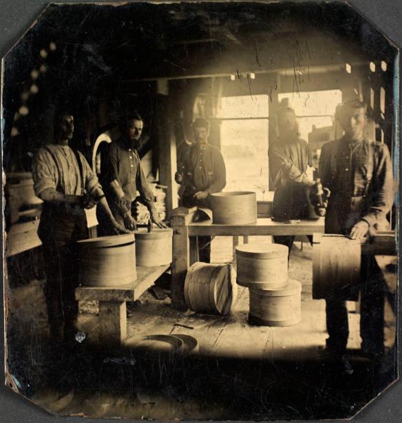 Une photographie en noir et blanc montrant cinq hommes en train d'assembler des boîtes en bois à l'intérieur d'un moulin.