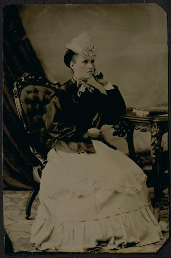 Portrait en noir et blanc, coloré à la main, d'une femme en position assise.