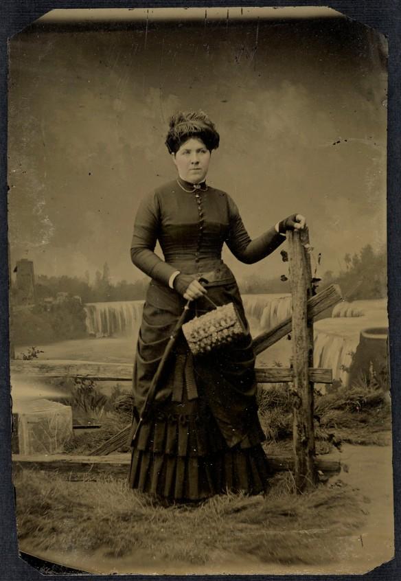 Portrait en noir et blanc, réalisé en studio, d'une femme non identifiée se tenant debout à côté d'une clôture avec les chutes Niagara en toile de fond.