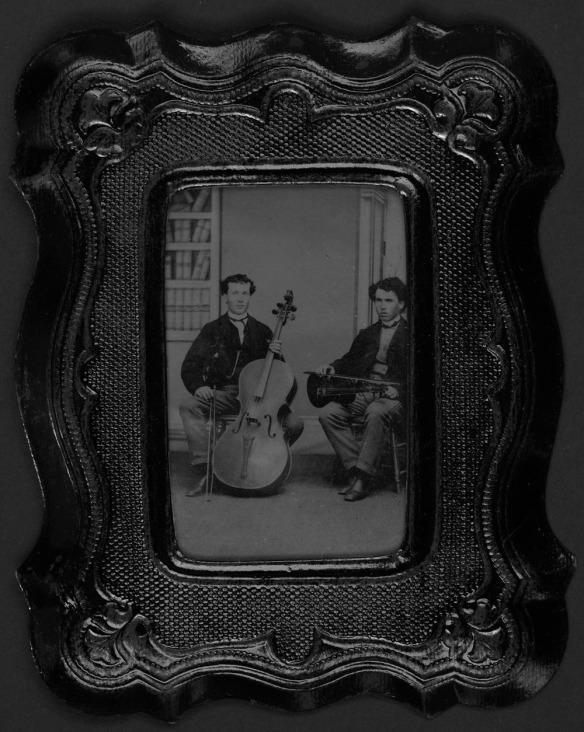 Portrait en noir et blanc de deux jeunes hommes en position assise. L'un d'eux tient dans ses mains un violon et l'autre, un violoncelle.