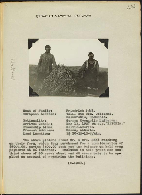 Petite photographie en noir et blanc d'un homme et d'une femme de chaque côté d'une balle de foin. Une description de la famille comprend leur nom, leur lieu d'origine, la façon dont ils sont arrivés, l'endroit où ils habitent et une brève description de leur ferme.