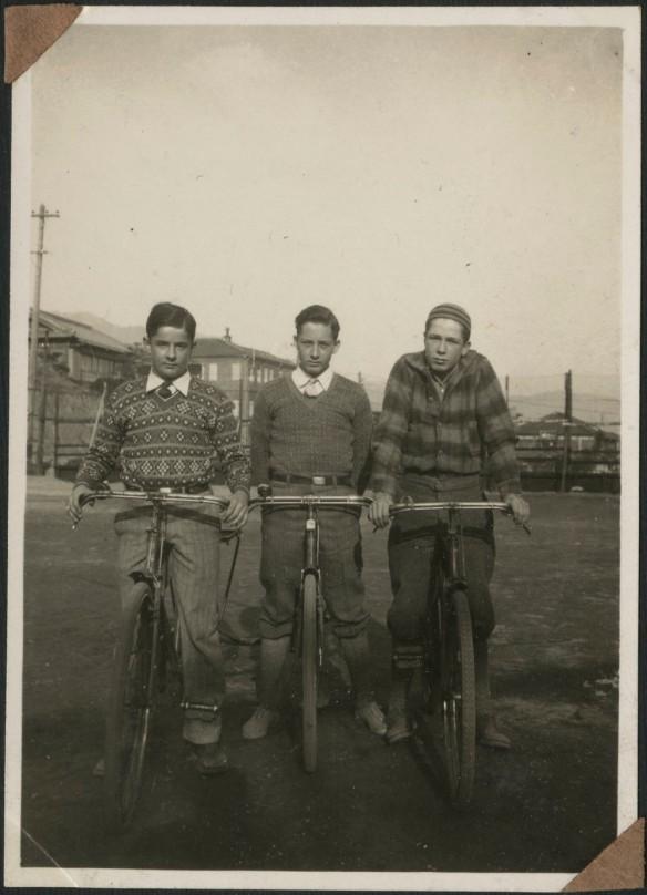 Photographie en noir et blanc montrant trois garçons sur des vélos.