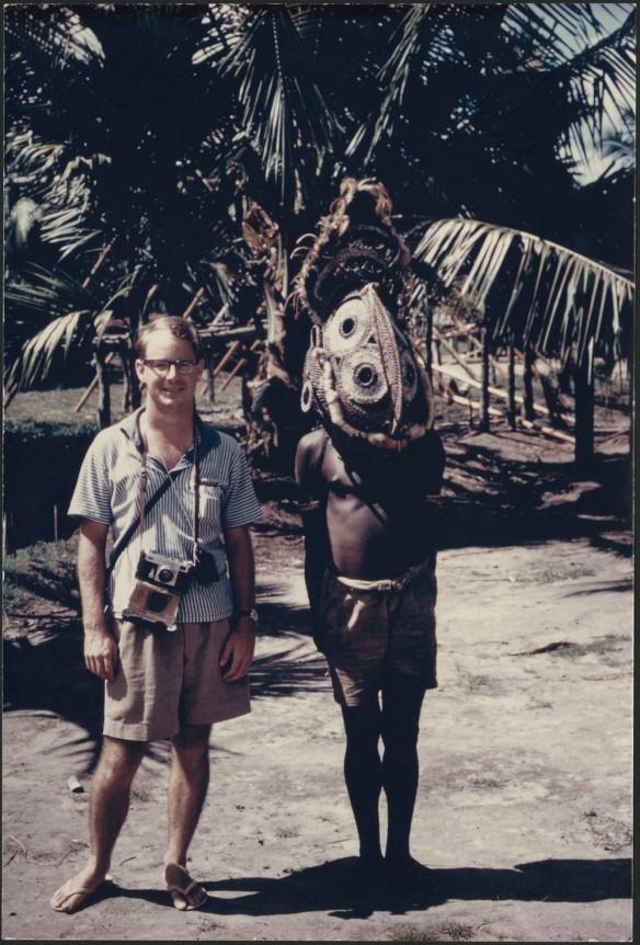 Photographie en couleurs d'un homme portant un short, une chemise et des sandales. Une caméra munie d'une courroie pend à son cou. Il se tient debout à côté d'un homme qui porte un short et un masque élaboré.